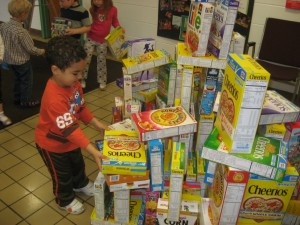 A child in the three year old program carefully adds to the building to block out hunger.